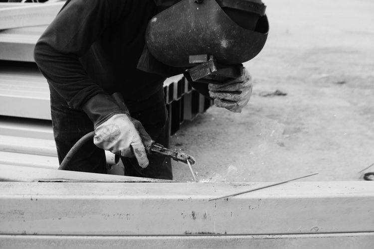 Manual worker welding with tool outdoor