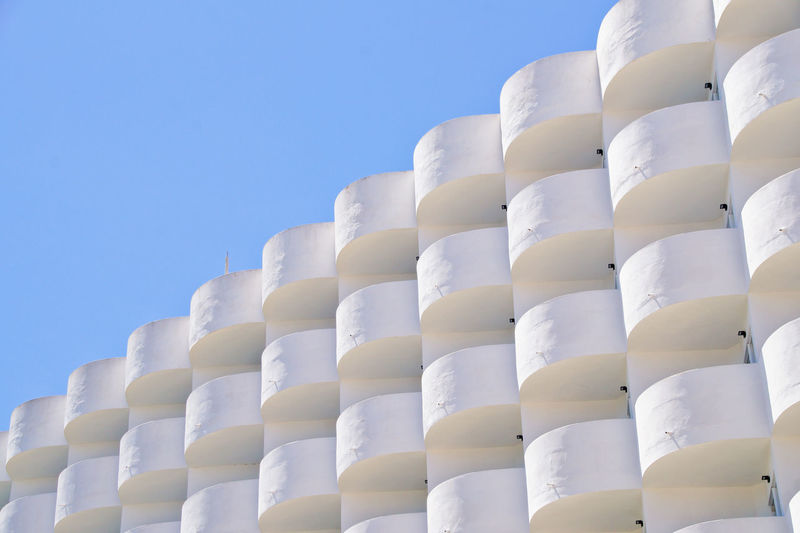 Low angle view of white hotel building against blue sky, cala d'or, mallorca