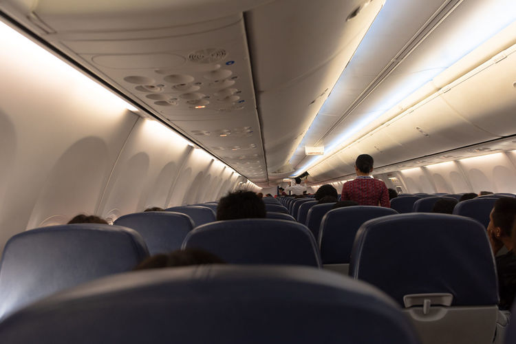 Adult Air Vehicle Airplane Airplane Seat Ceiling Group Of People In A Row Indoors  Lifestyles Men Mode Of Transportation People Real People Rear View Seat Sitting Transportation Travel Uniform Vehicle Interior Vehicle Seat Women