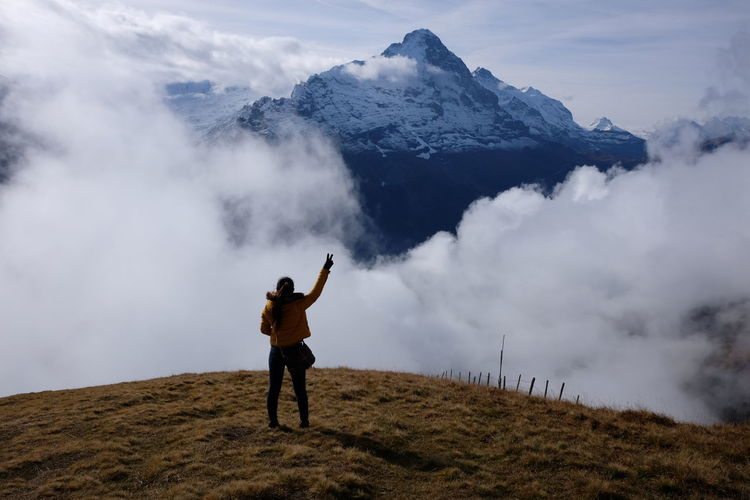 Rear view of woman standing on mountain peak against sky
