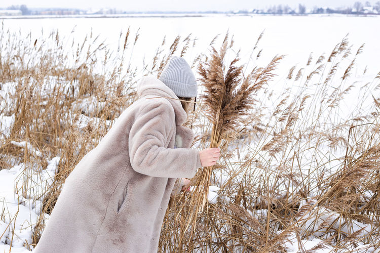 Midsection of woman standing on snow covered field
