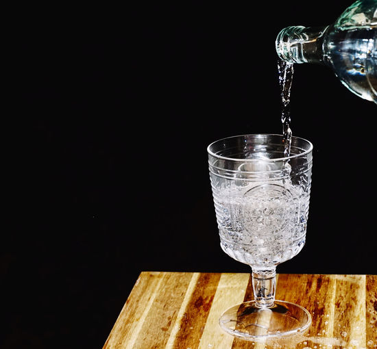 Close-up of wineglass on glass against black background