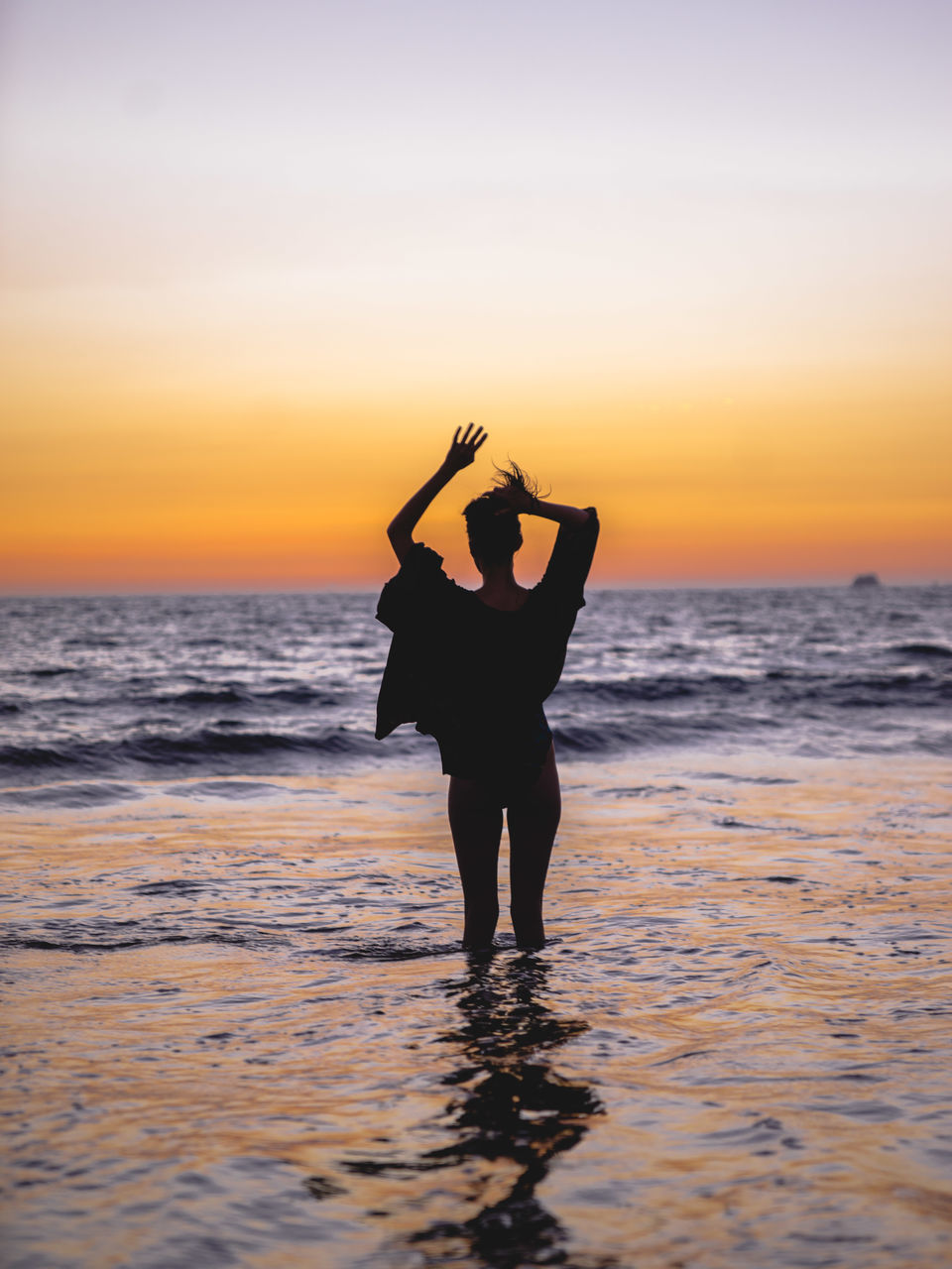 Rear View Of Woman With Hand In Hair While Standing In Sea Against Sky During Sunset