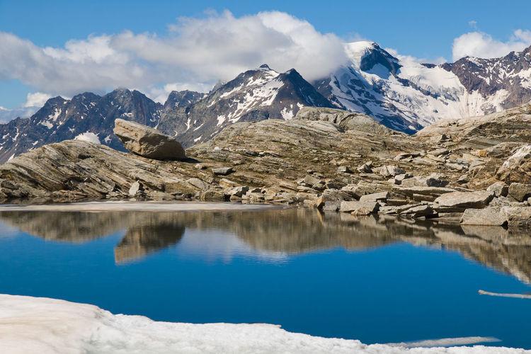 Colorful emerald lake lago smeraldo in the italian alps with monte rosa in the background