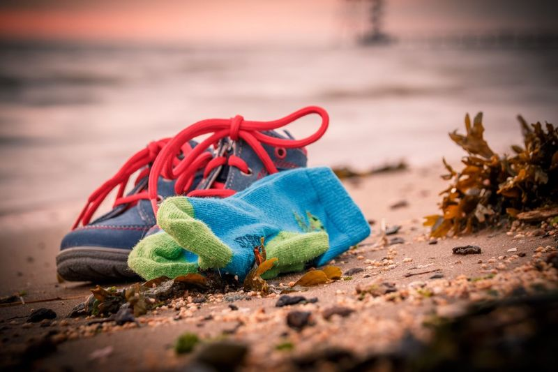Close-Up Of Shoes And Socks On Sand At Beach