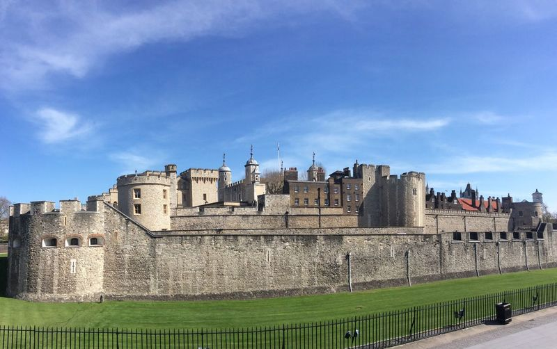 Royal Palace and Fortress of the Tower of London, is a historic castle in London, United Kingdom. Royalty Afternoon Lawn Fortified Wall The Past Thames River Surrounding Wall European  Uk Tower Of London Palace Horizontal Tower Stone Material Fort No People Medieval History Gothic Style Castle Architecture Urban Skyline Copy Space Sky And Clouds Green Color