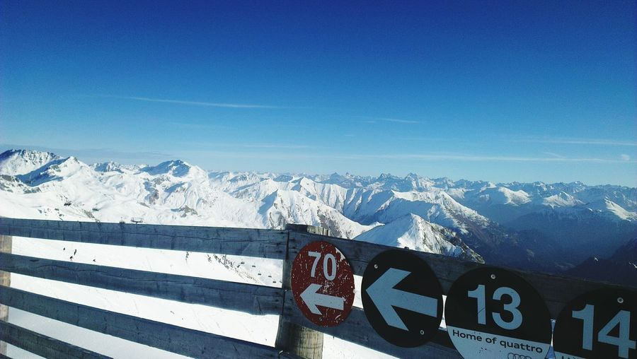 Signs on wooden railing at snowcapped mountain against blue sky