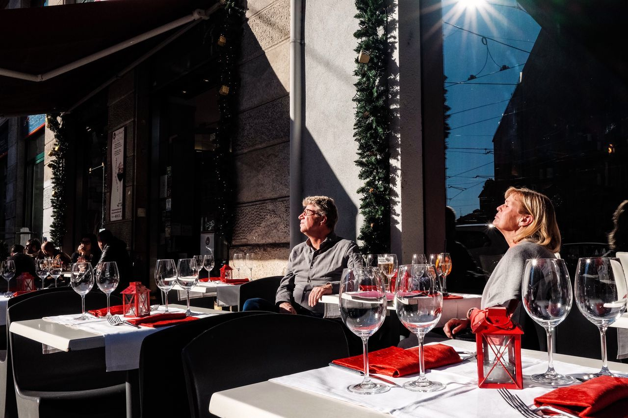 table, wineglass, restaurant, wine, real people, food and drink, drink, chair, drinking glass, cafe, sitting, place setting, lifestyles, building exterior, alcohol, day, outdoors, women, two people, blond hair, architecture, young adult, young women, adult, people