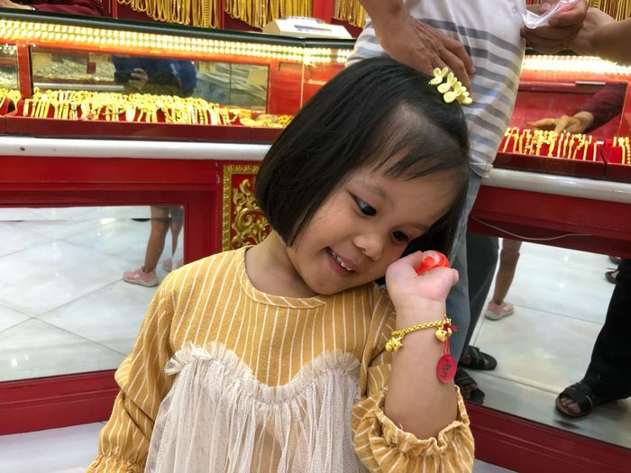 Portrait of cute girl in traditional clothing gold bracelet pay