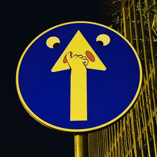 Close-up of road sign against blue sky