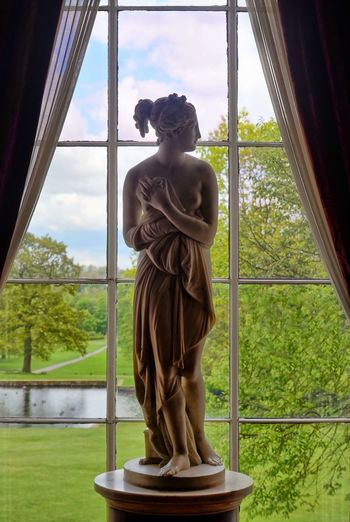 Statue against sky seen through window