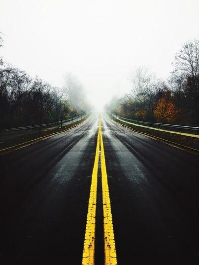 Road amidst trees against sky during rainy season