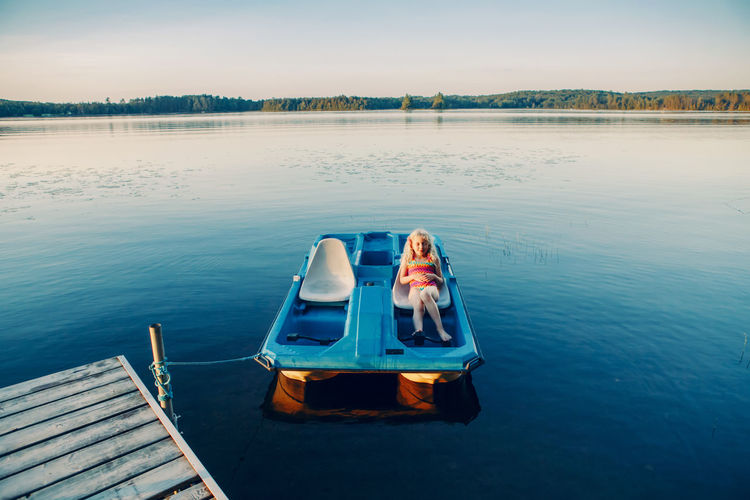 Woman sitting in boat on lake