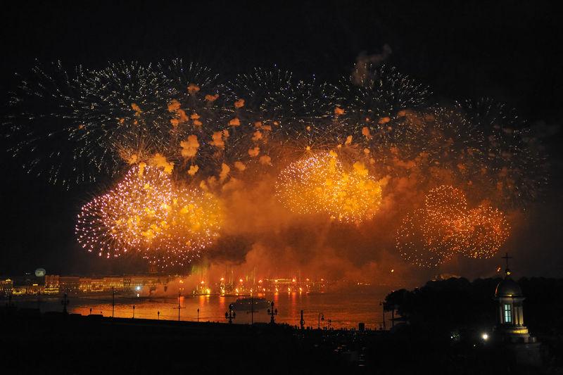 Firework display over lake at night during scarlet sails