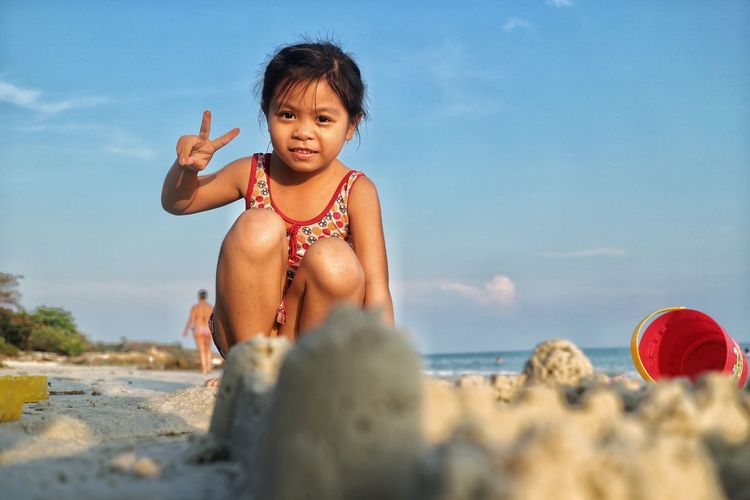 Portrait of girl gesturing peace sign at beach