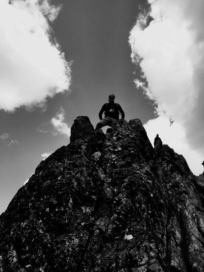 Low angle view of man standing on cliff against sky