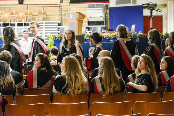 Graduate students at De Montfort Hall of the University of Leicester, UK. Graduation Rear View Students United Kingdom Academic Adult Audience Editorial  Education Grads Graduate Group Of People Hall Indoors  Men Real People Sitting Togetherness University University Of Leicester Women
