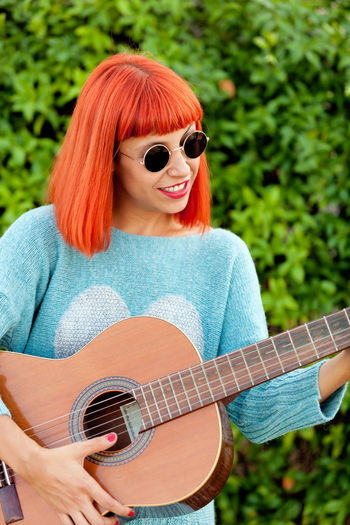Smiling woman playing guitar standing by plants outdoors