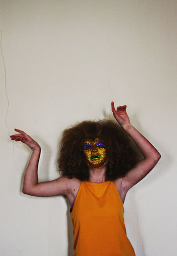 Arms Raised Body Part Canon Childhood Copy Space Curly Hair Fashion Front View Fun Hair Hairstyle Human Arm Human Body Part Human Limb Indoors  Limb Mask One Person Portrait Standing Studio Shot Waist Up Wall - Building Feature White Background Yellow
