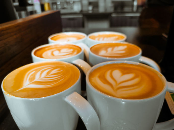Close-up of cappuccinos served on table
