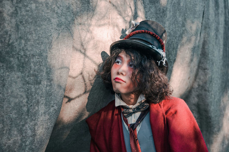 Portrait of young man cosplaying mad hatter looking away against statue