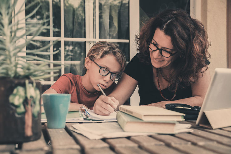 Mother helping boy in study at home