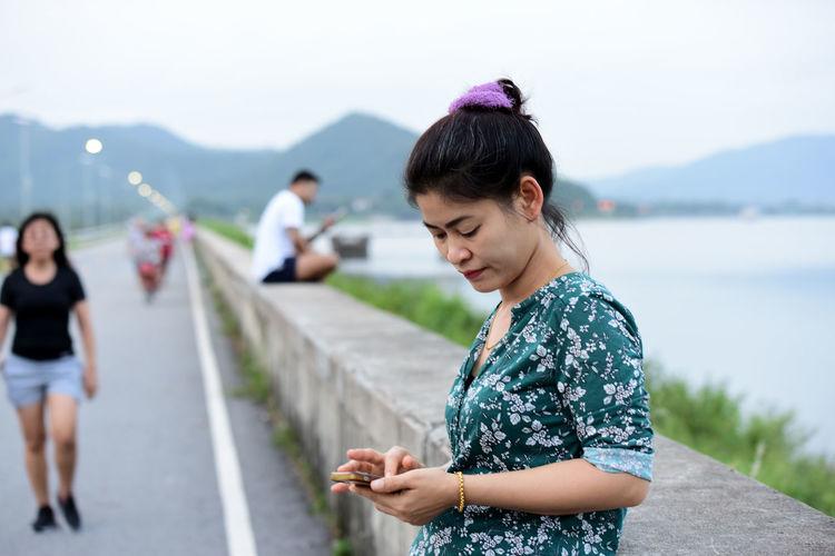 Beautiful happy woman using phone by lake