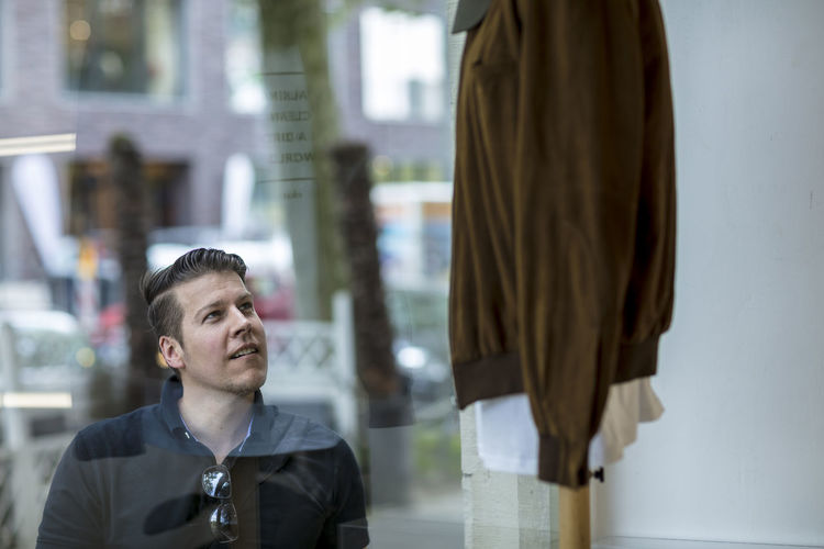 Man window shopping at a clothing store. A sweater hangs on display. City scenery in the background. Medium close up shot. Adult Man Sunny Window Shopping Afteroon Casual Clothing Caucasian Clothing Day Golf Shirt Good Looking Handsome Male Medium Close Up Model Outdoors Outside Portrait Posing Store Store Window Summer Sweater Urban Window