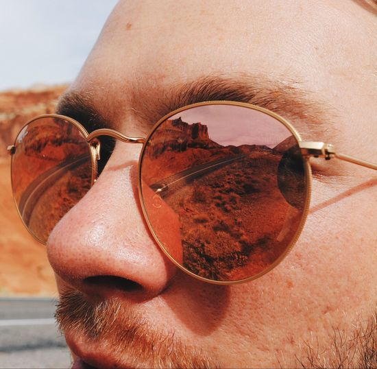 Cropped image of man wearing sunglasses with reflection