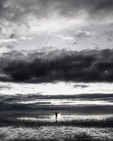 Silhouette person standing on shore by sea against sky