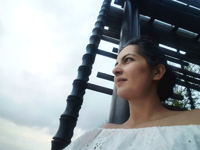 Low angle view of thoughtful woman against sky