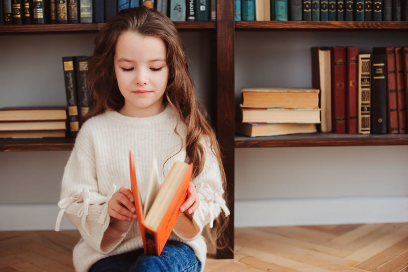 Cute Girl Opening Book While Sitting At Home