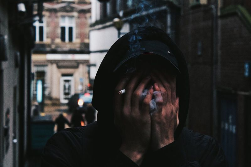 Close-Up Of Man Smoking Cigarette While Covering Face With Hands