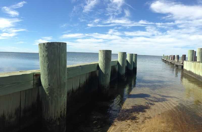 Wooden Post By Pier In Sea Against Sky