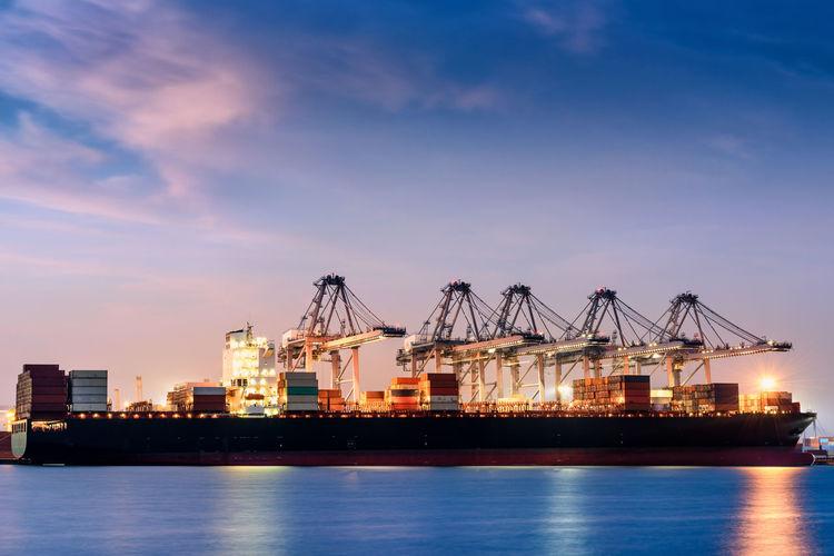 Cranes at commercial dock against blue sky