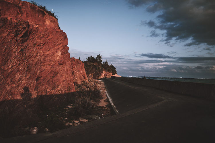 Road by rock formation against sky