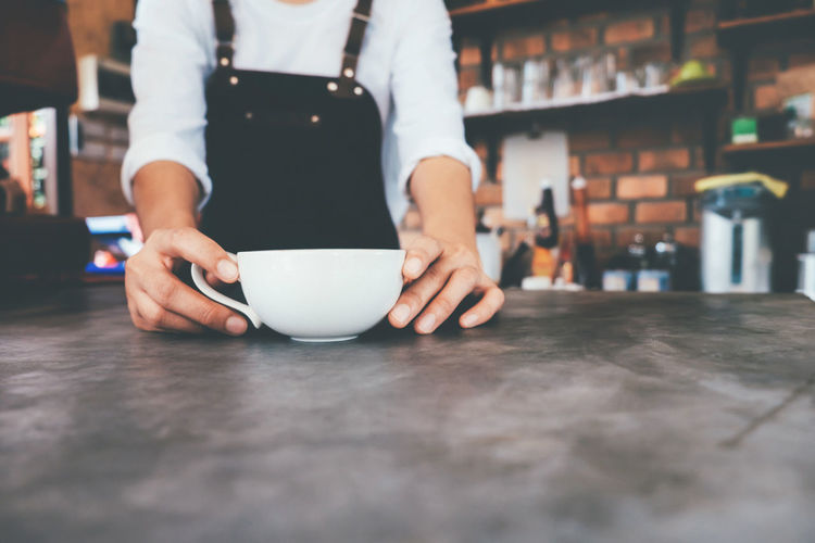 Midsection of barista serving coffee at table in cafe