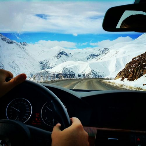 Cropped image of person driving car on road towards snow covered landscape