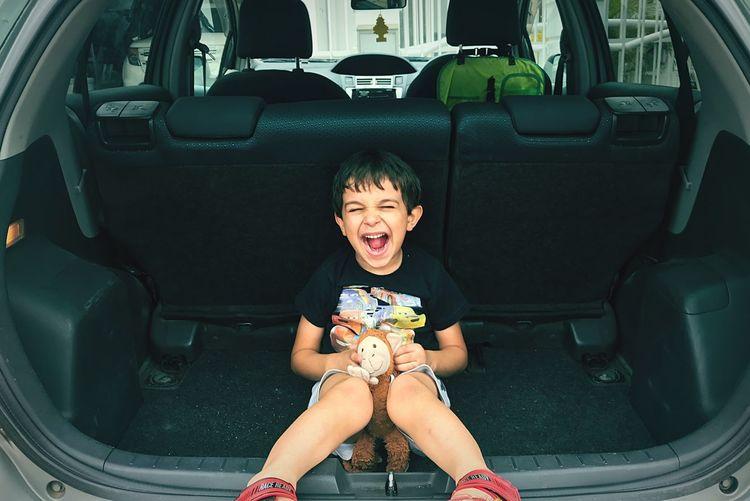 Full length of boy sitting in car