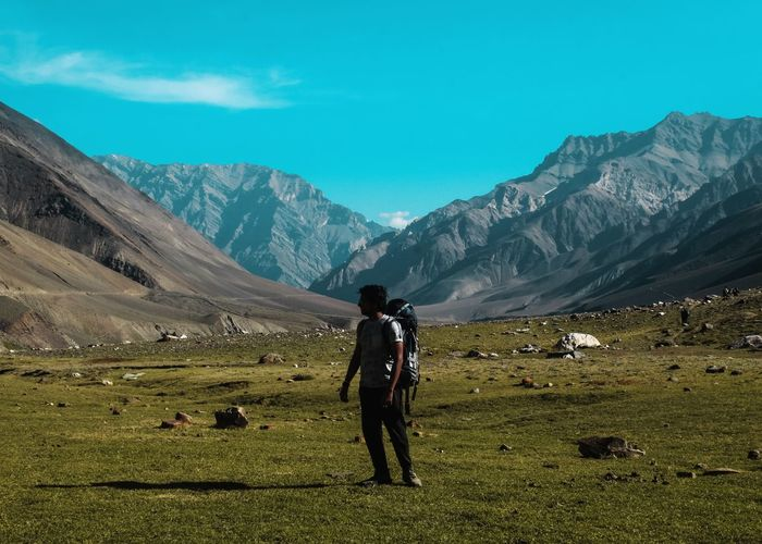 Rear view of man on field against mountains