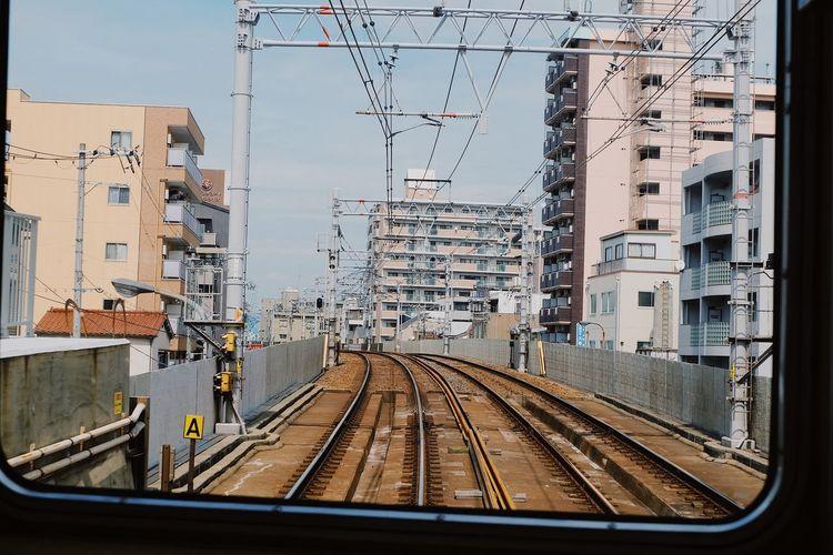 Railroad tracks and buildings seen through train window