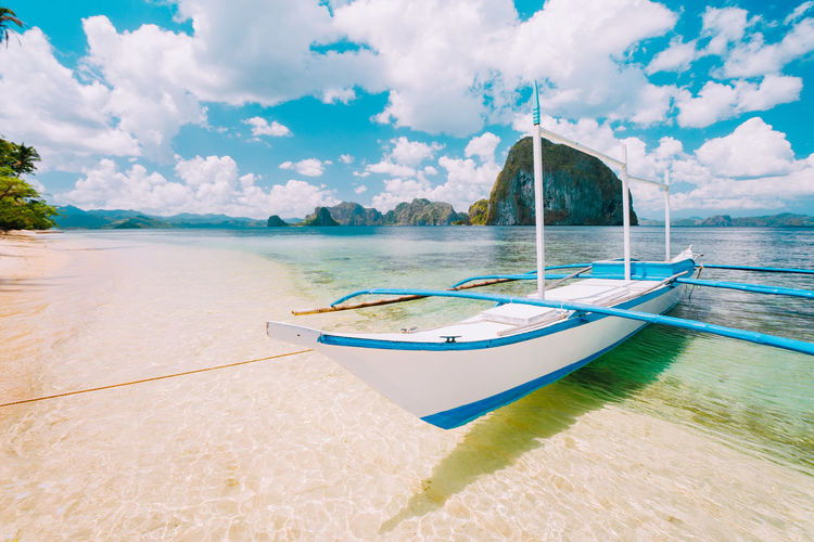 White banca island hopping boat at Las cabanas beach with amazing Pinagbuyutan island in background. Beautiful landscape scenery in El Nido, Palawan, Philippines. El Nido, Palawan Philippines Travel Destinations Paradise Tropical Summer Tourism Ocean Beach Palmtree Azure Turquise Water Banca Boat Jorney Destanations Remote Places Famous Place Transparent Island Hopping Aktivity Foliage, Vegetation, Plants, Green, Leaves, Leafage, Undergrowth, Underbrush, Plant Life, Flora Bright Colors Blue Lagoon Water Nautical Vessel Cloud - Sky Sky Sea Transportation Mode Of Transportation Scenics - Nature Moored Day Beauty In Nature Nature Land Tranquility No People Tranquil Scene Outrigger Idyllic Outdoors Horizon Over Water Turquoise Colored Sailboat Pinagbuyutan