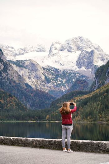 Rear view of woman standing on mountain by lake taking a picture