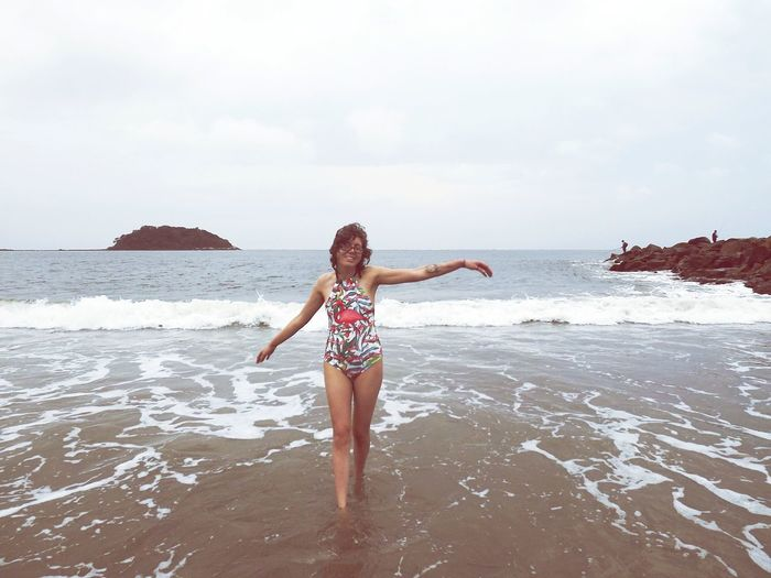 Smiling Mid Adult Woman With Arms Outstretched Standing At Beach