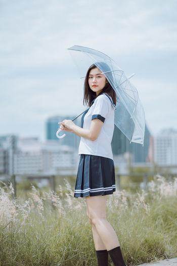Portrait of young woman with umbrella standing by plants on field