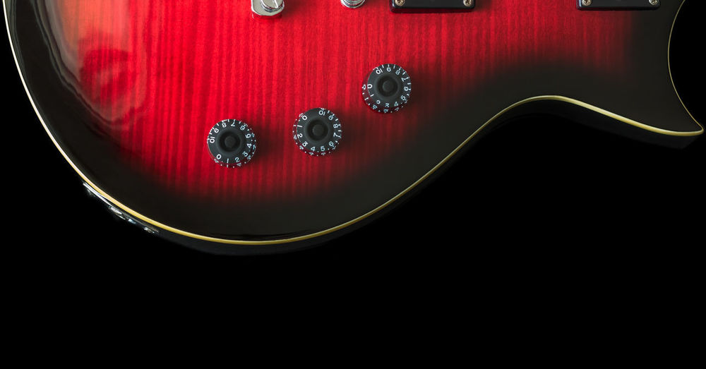 A black and red guitar in a sunburst finish. This image showcases the overall shape and lines of the instrument. There is plenty of copy space. Audio Copy Space Lines Maple Wood Music Objects Red Shape Wood Abstract Accessories Art Backgrounds Black Card Close-up Concept Contrast Design Details Electricity  Flamed Maple Guitar Instrument Knobs