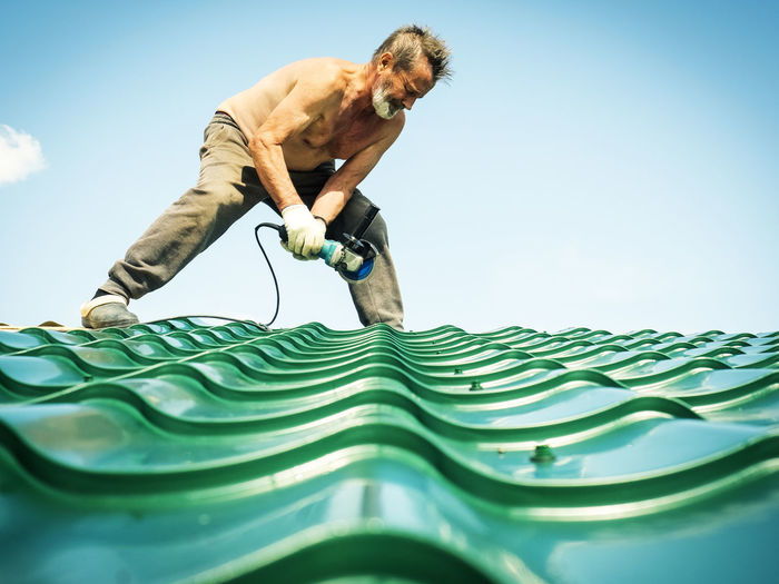 Shirtless Man Working On Roof Against Sky