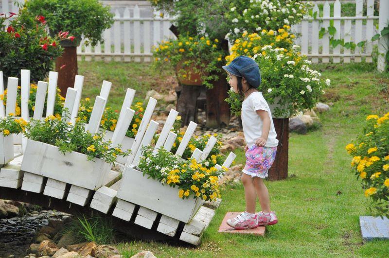 Side view of girl holding flower pot - girl walking on bridge in the garden