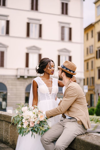 Couple embracing while sitting against building