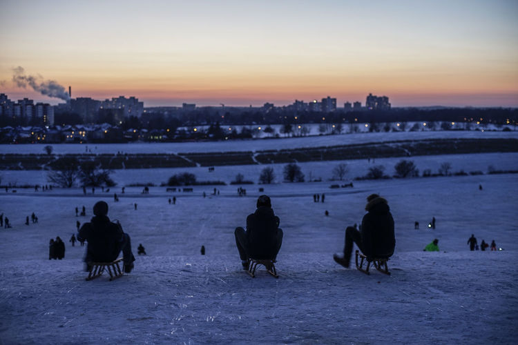 People on snow covered cityscape against sky during sunset